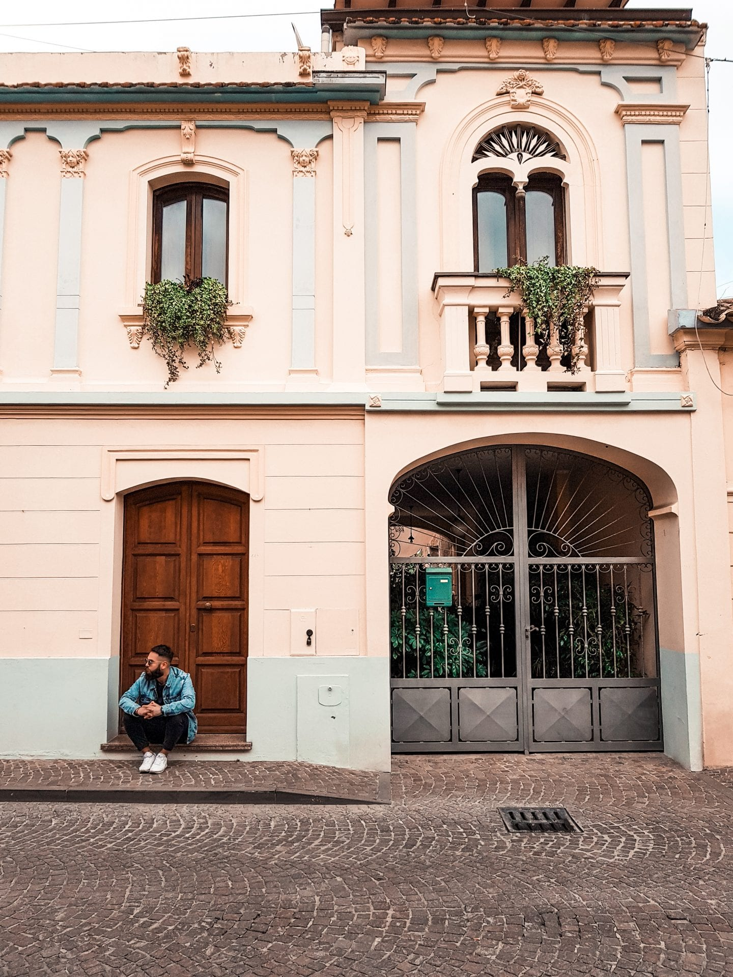 boy sitting in front of an house in italy