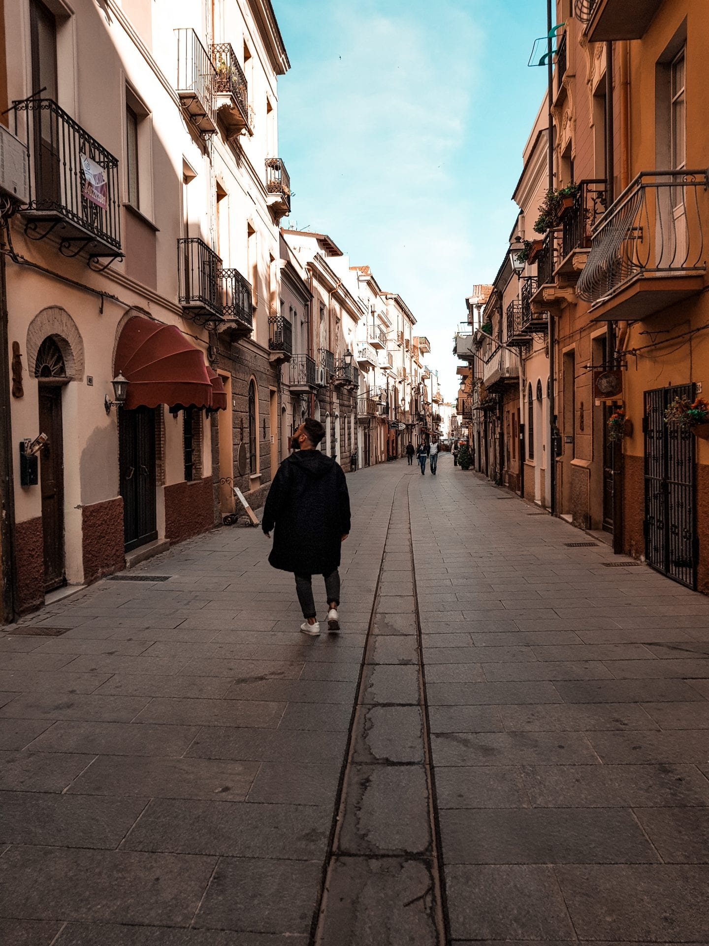guy walking through small italian city