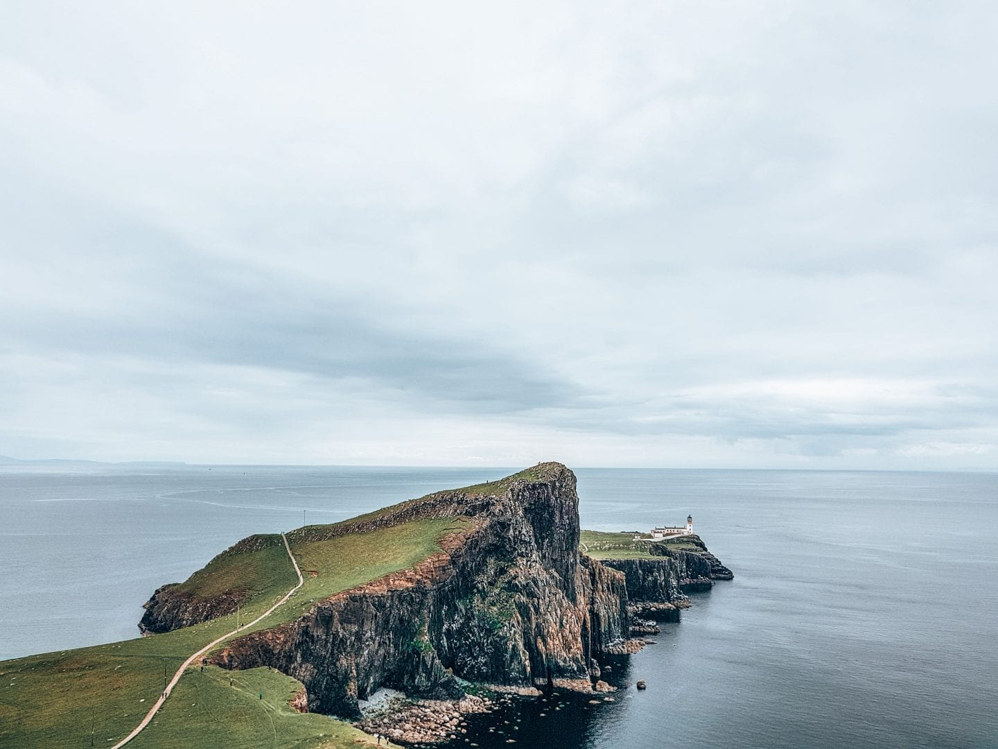 lighthouse on a cliff in front of the sea in scotland