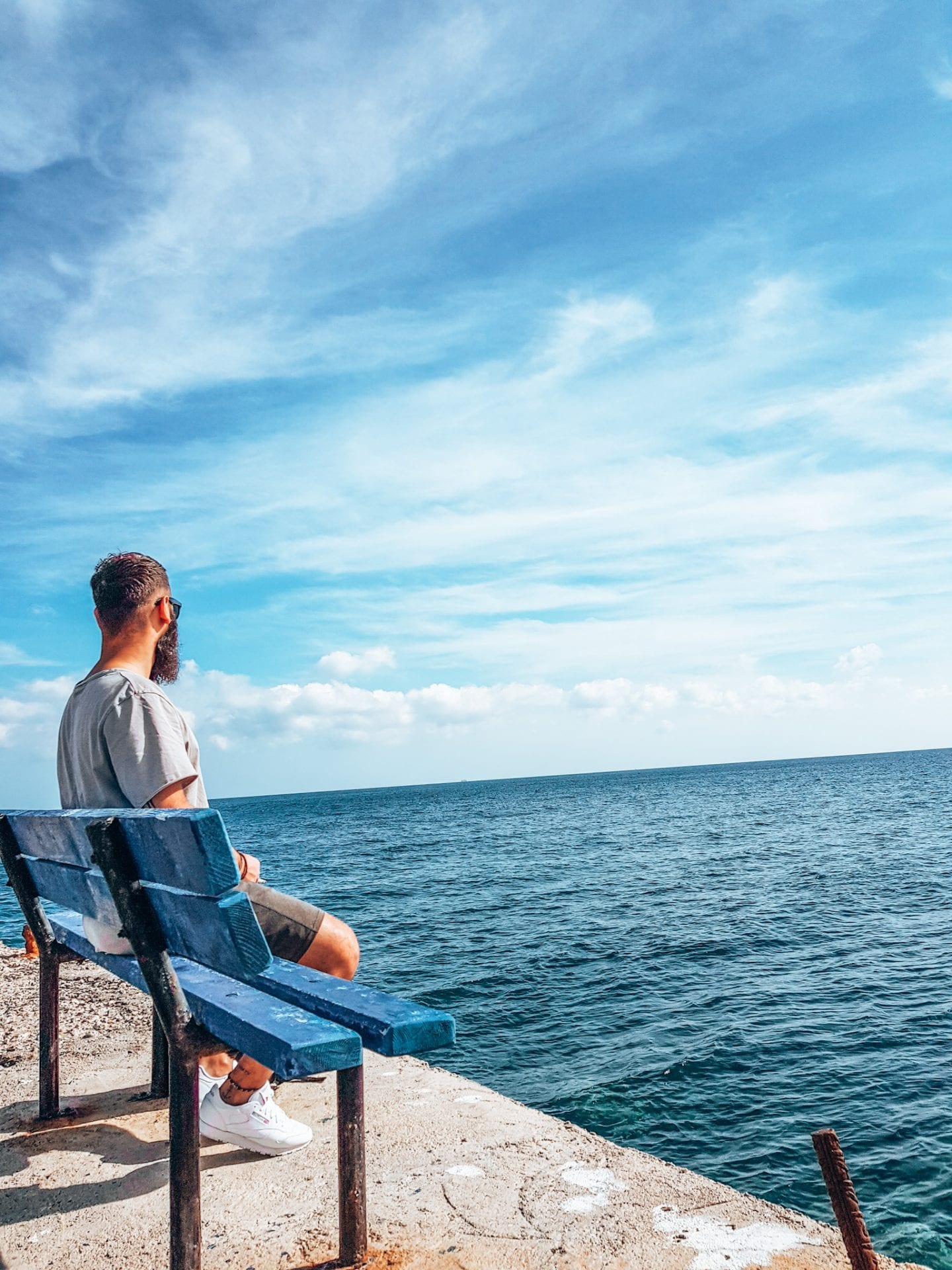 boy sitting on bench in front of sea