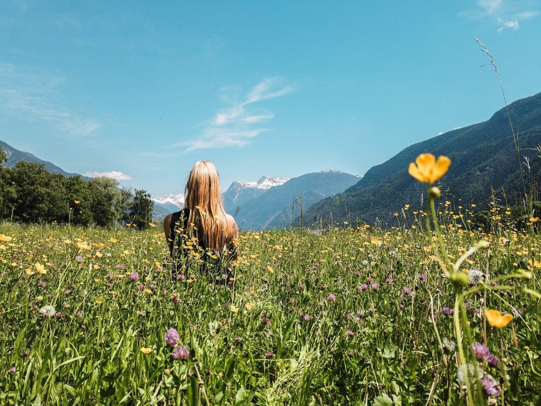 Miriam sitzt auf einer bunten Blumenwiese, im Hintergrund sieht man die schneebedeckten Berge des Wallis, Schweiz.