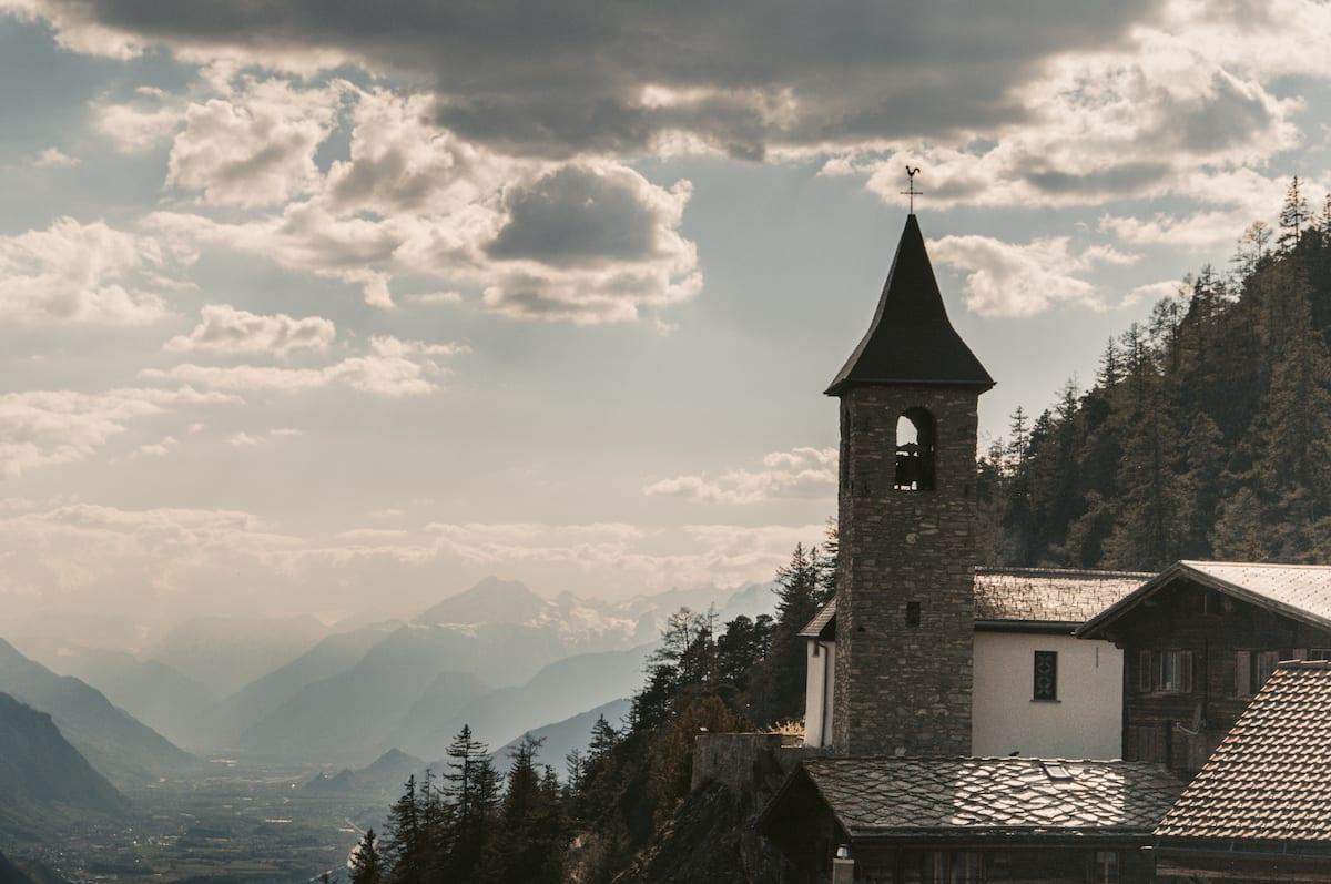 Kirchenturm in Guttet im Wallis. Im Hintergrund ist eine umrisshafte Bergkulisse zu erkennen.