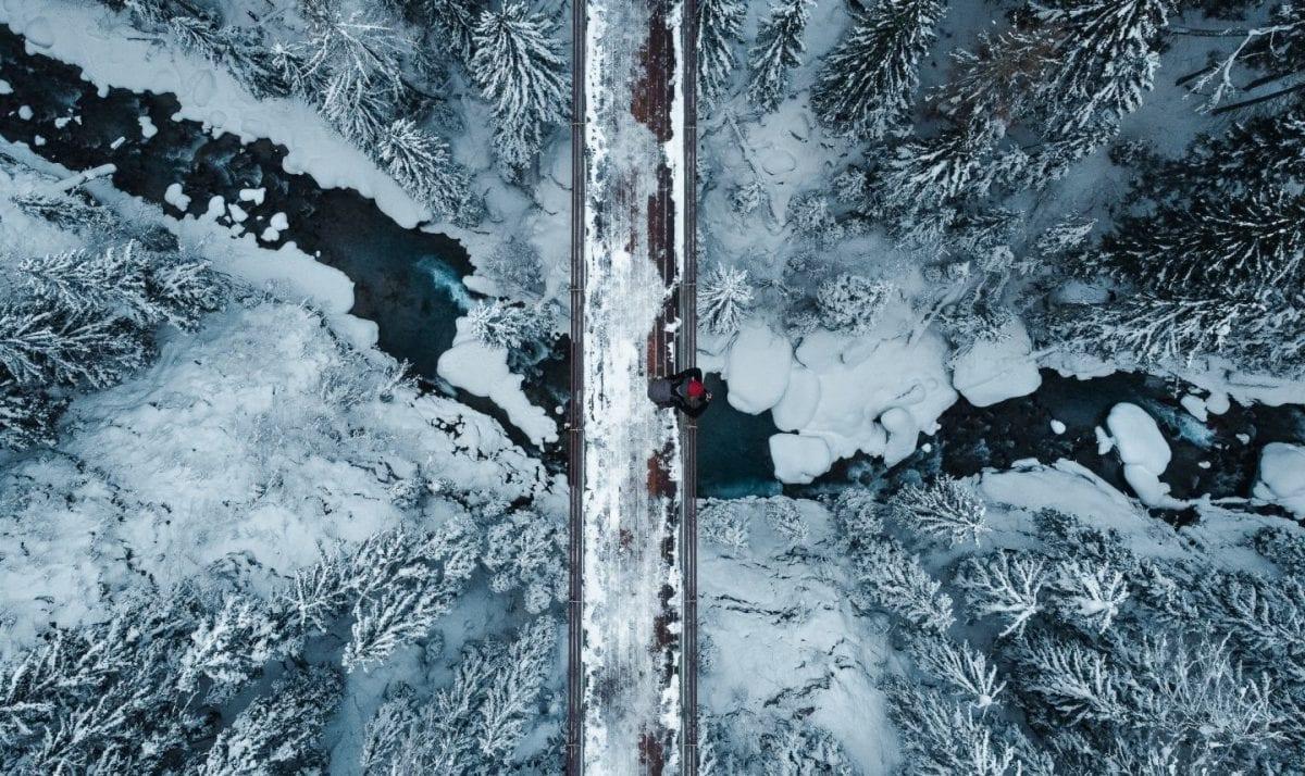 Die GOMS Bridge aus der Vogelperspektive. Miriam steht auf der Brücke, darunter der Rotten und schneebedeckte Baumwipfel