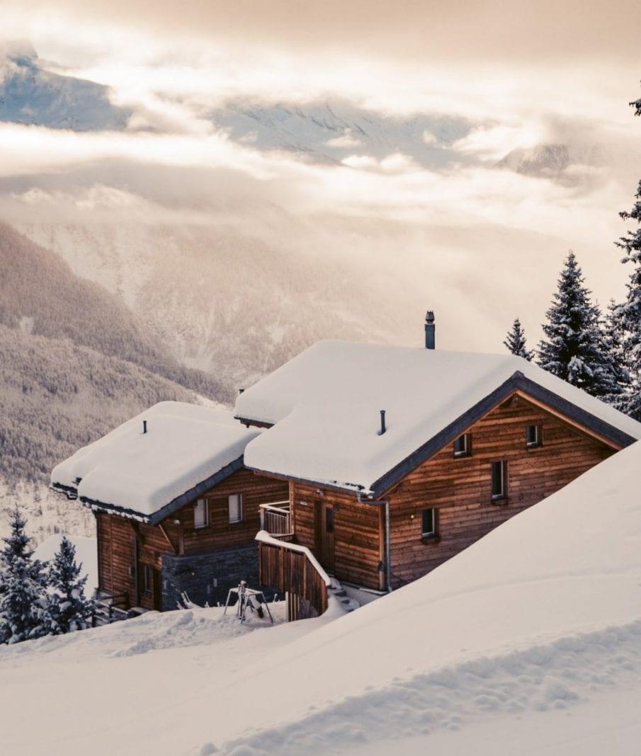 Chalets in der Aletscharena vor einem Alpenpanorama.