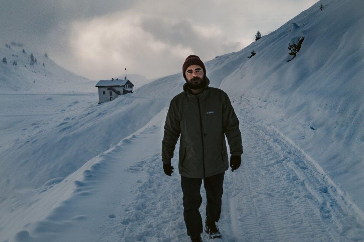 Bertal geht durch den Schnee auf einem Winterwanderweg in der Schweiz. Hinter ihm ist in der Ferne ein kleines Haus zu sehen.