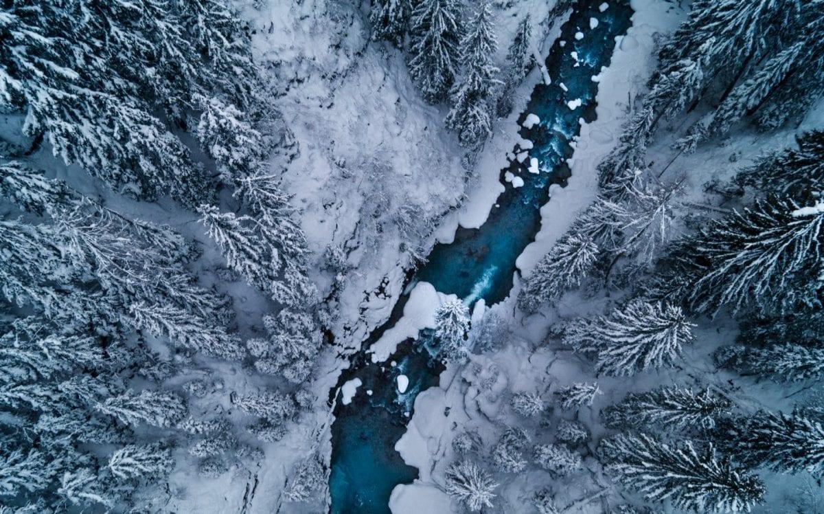 Bild von der GOMS Bridge auf die Rhone und schneebedeckte Tannen.