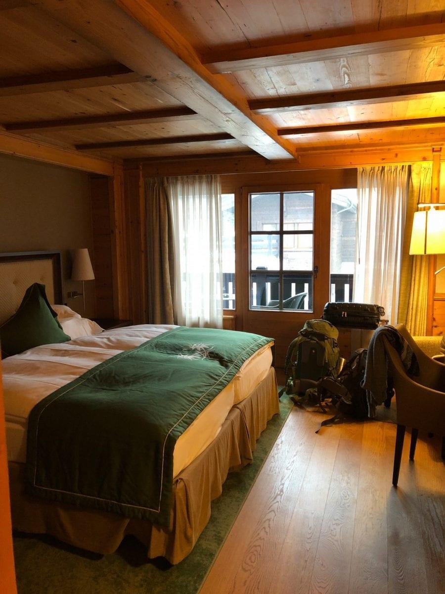 Das Zimmer im Riffelalp Resort. Links ein großes Bett, rechts ein gemütlicher Stuhl. Im Hintergrund der Balkon.