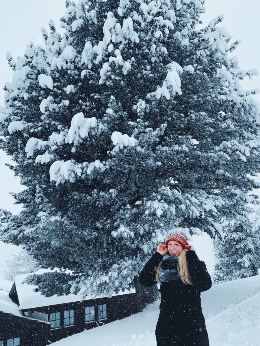 Miriam in Winterkleidung im Schnee vor einem großen Baum