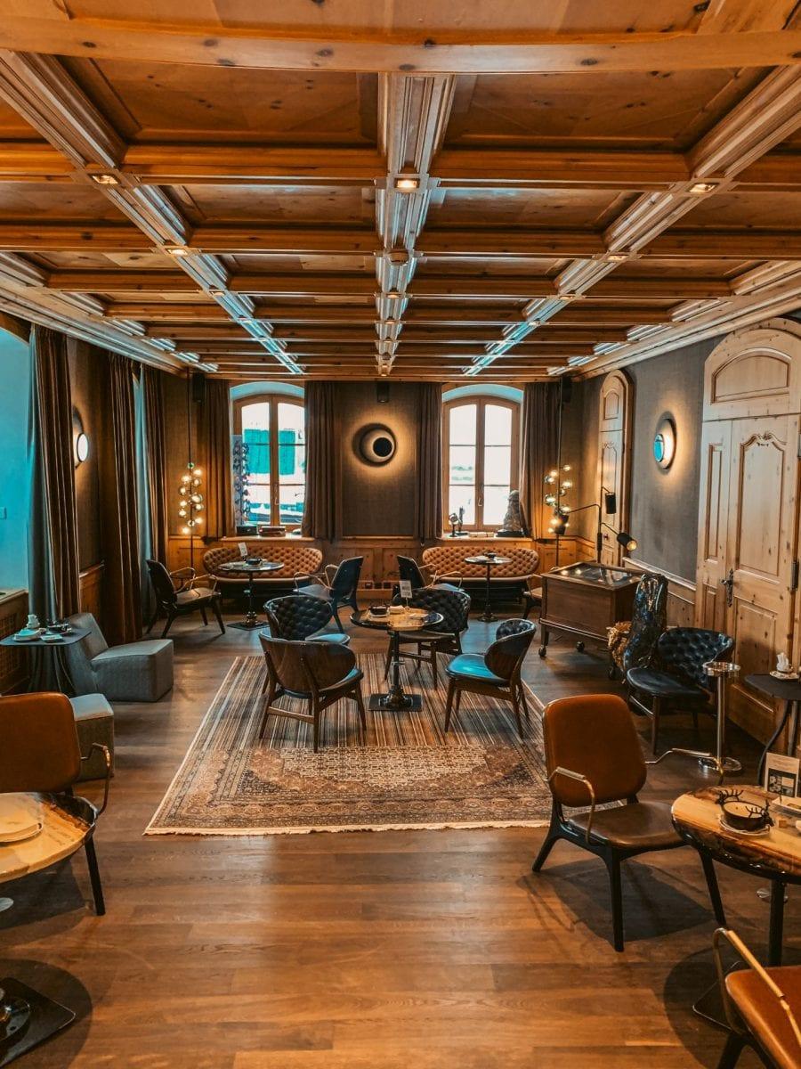 Raucherlounge im Riffelalp Resort. Klassisch eingerichtetes Zimmer mit gemütlichem Lihct und holzvertäfelter Decke