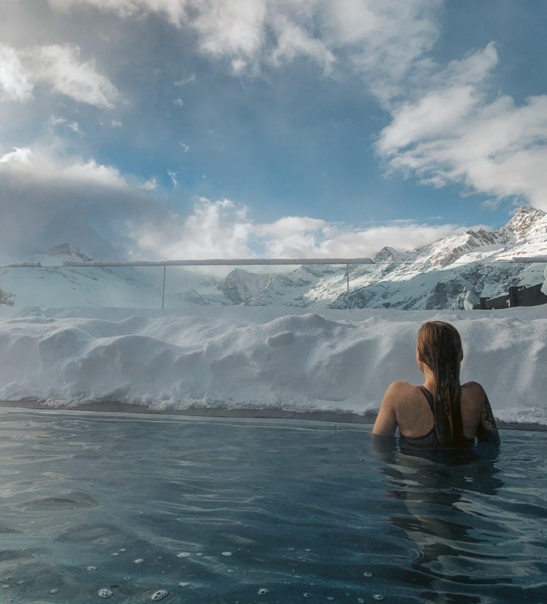 Miriam schwimmt im Outdoor Pool des Riffelalp Resorts mit Blick auf die schneebedeckten Berge