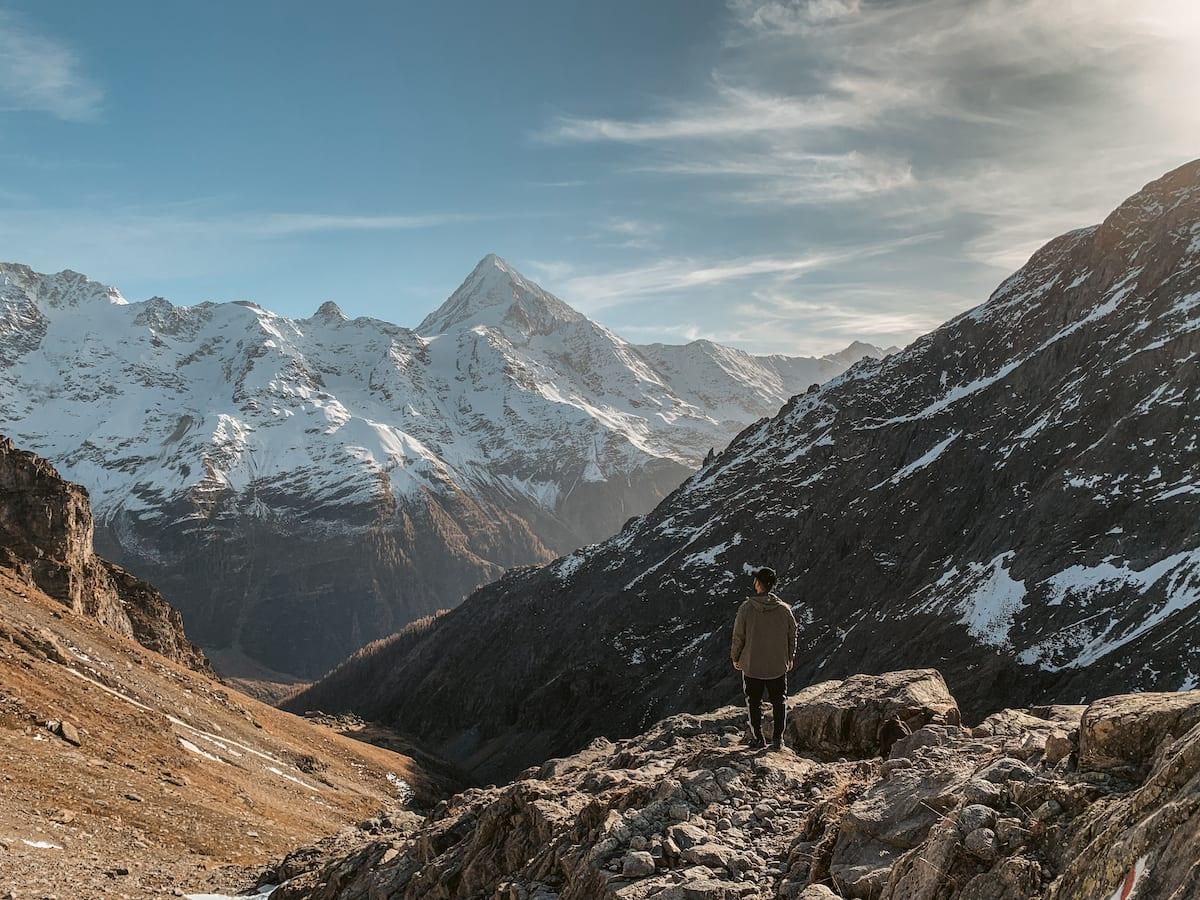 Bertal steht mit dem Rücken zur Kamera vor den schneebedeckten Bergen im Lötschental