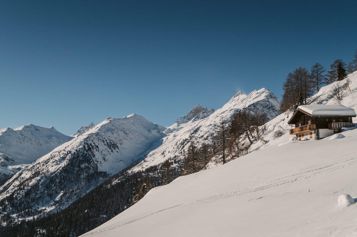 Ein kleines Chalet am schneebedeckten Hang im Lötschental.Aussicht auf schneebedeckte Berggipfel.