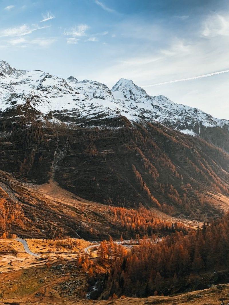 Aussicht ins herbstliche Lötschental mit schneebedeckten Bergen und roten Lärchen.