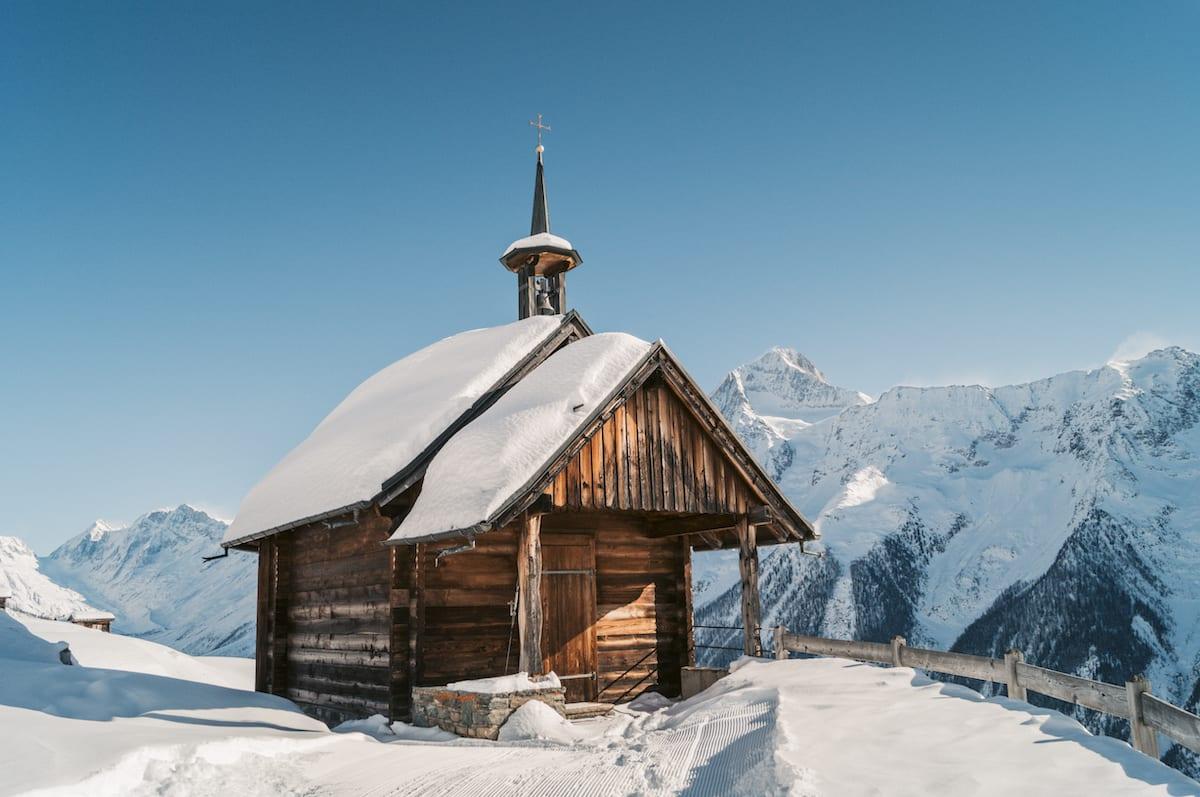 Hölzerne schneebedeckte Kirche vor blauem Himmel und schneebedeckten Bergen