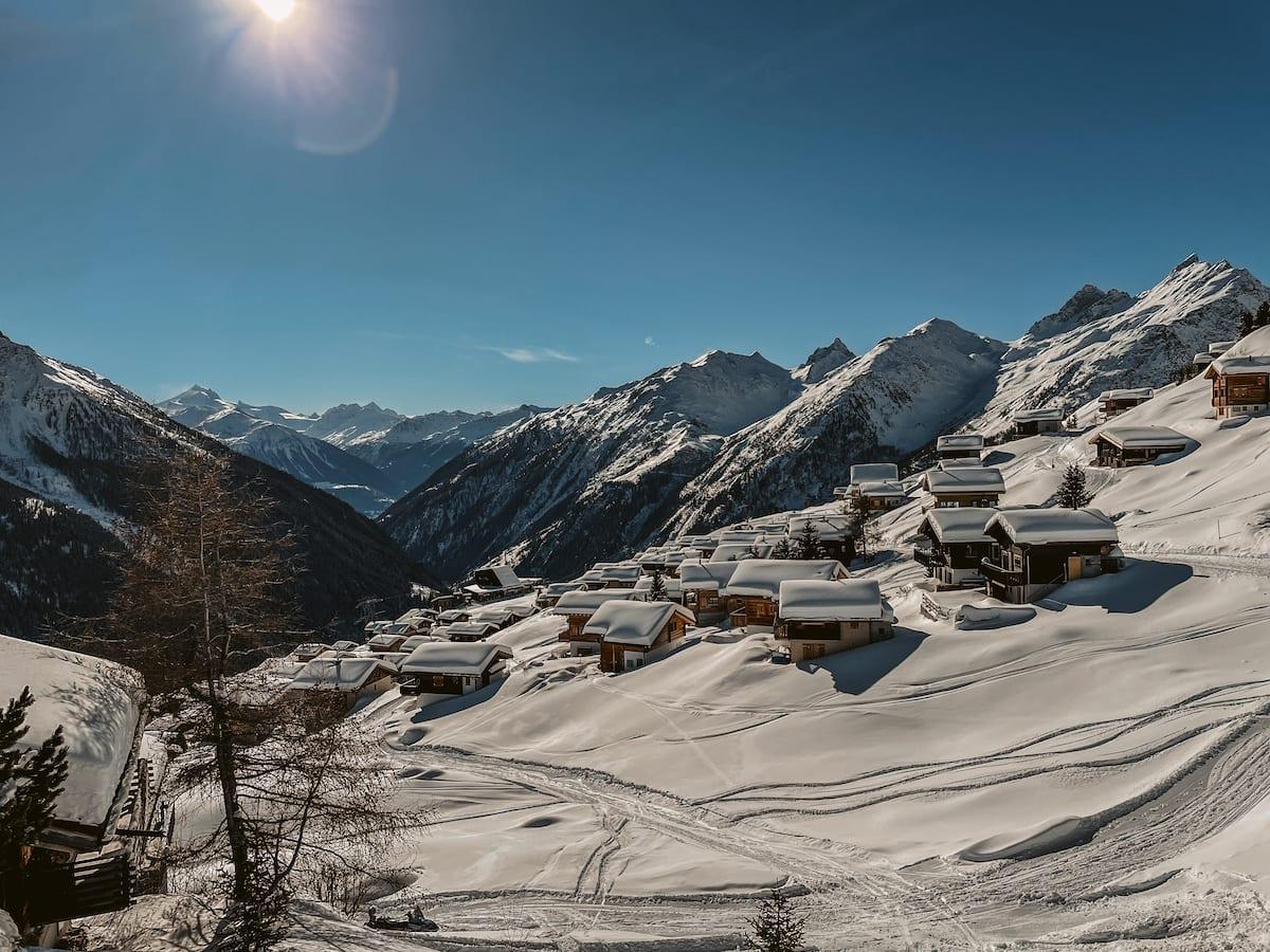 Blick über die Lauchernalp im Lötschental. Viele kleine, schneebedeckte Häuser vor einem weitläufigen Alpenpanorama.