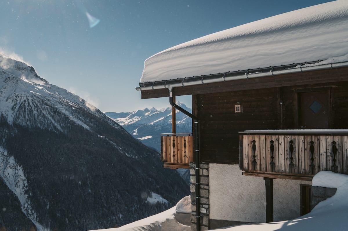 Haus vor einem Panoramaausblick mit schneebedeckten Gipfeln im Lötschental