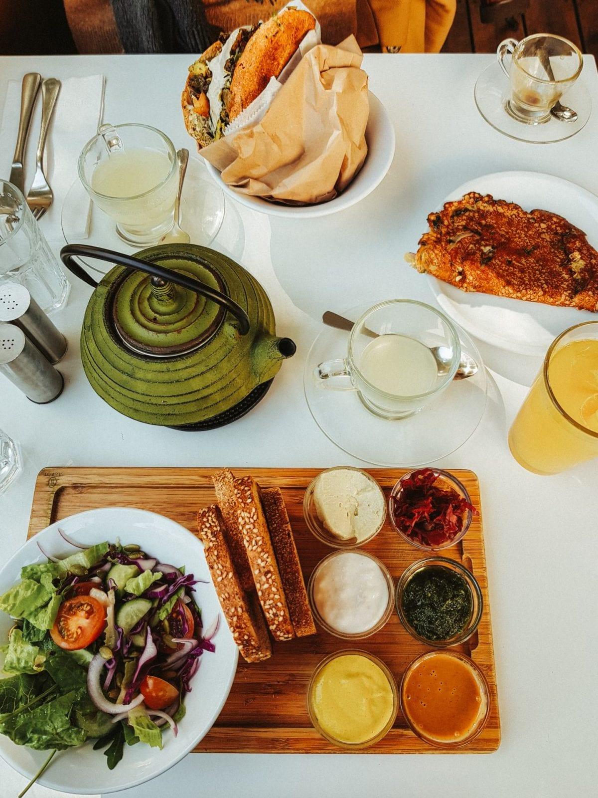 Veganes Frühstück im restaurant Anastasia in Tel Aviv. Salat, Brot mit verschiedenen Aufstrichen, Sandwich, tee.