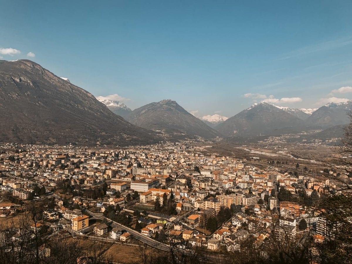 Aussicht über Domodossola vom Sacro Monte aus. Im Hintergrund sind hohe Berge zu erkennen.