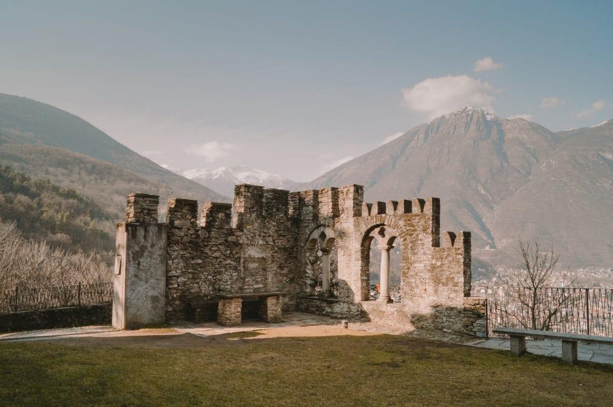 Teile einer Burgruine auf dem Sacro Monte in Domodossola. Im Hintergrund erkennt man einige Häuser und hohe Berge.