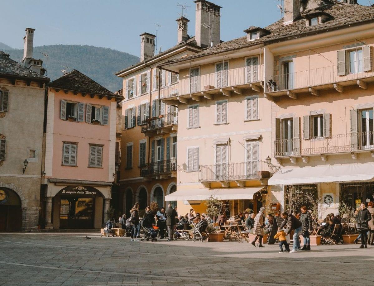 Bunte Häuser und Menschen auf dem belebten Marktplatz von Domodossola.