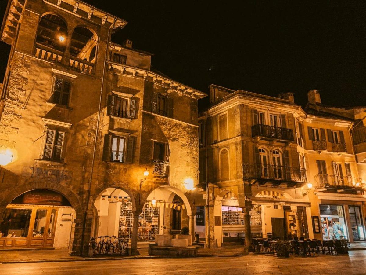 Alte Häuser am Marktplatz in Domodossola. Der Himmel ist dunkel, die Häuser warm beleuchtet.