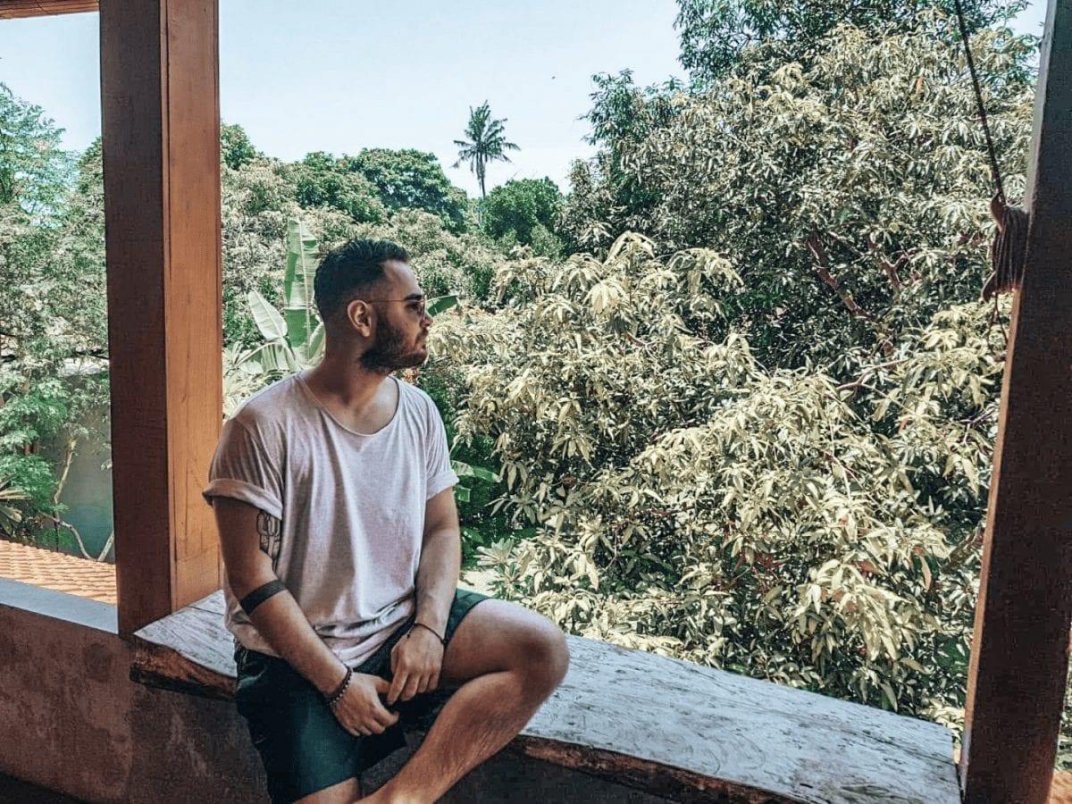 bertal sitzt auf der balkonterasse mit blick auf den dschungel in pererenan auf bali